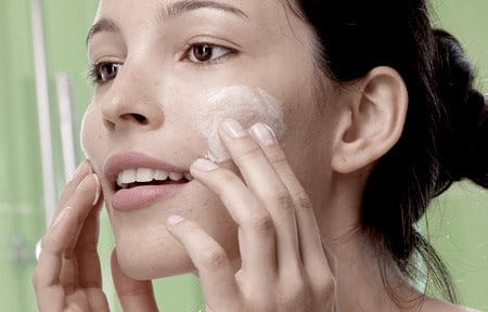 Woman applying skin care on her face