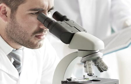 Scientist looking through microscope.