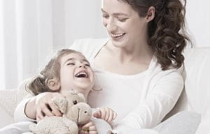 Little girl, laughing and holding a stuffed animal is sitting on her mom´s lap.