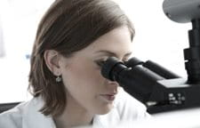 Woman looking into the microscope