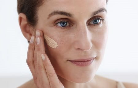 Woman applying Hyaluron-Filler CC Cream