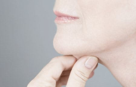 Woman pulling her chin skin with hand