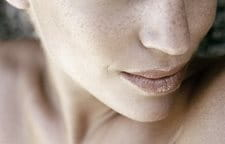 Lower part of a woman´s face with freckles.