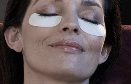 Woman´s face with care pads under her eyes.