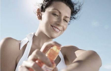 Woman applying sun spray on her forearm