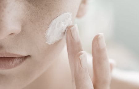 Woman is applying cream on her left cheek with finger.