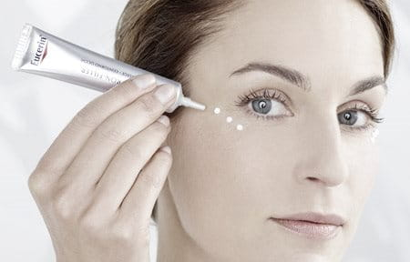Woman applying dropwise cream on her right cheekbone.