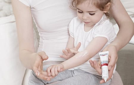 Little girl, sitting on mother´s lap, is applying Eucerin AtoControl Acute Care cream on the crook of her arm.