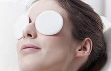 Woman relaxing with eye pads on both eyes.
