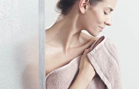 Woman pats her skin after showering