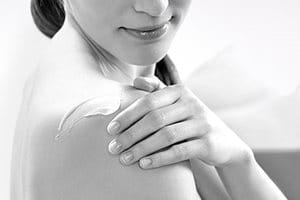 Woman applying cream on her shoulder.