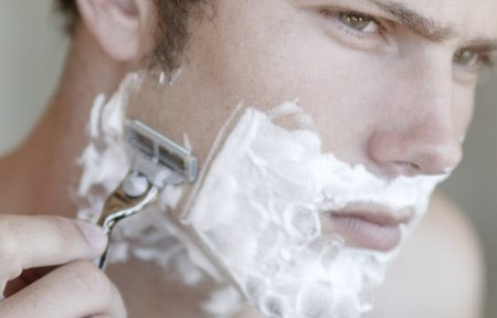 Man is wet shaving.