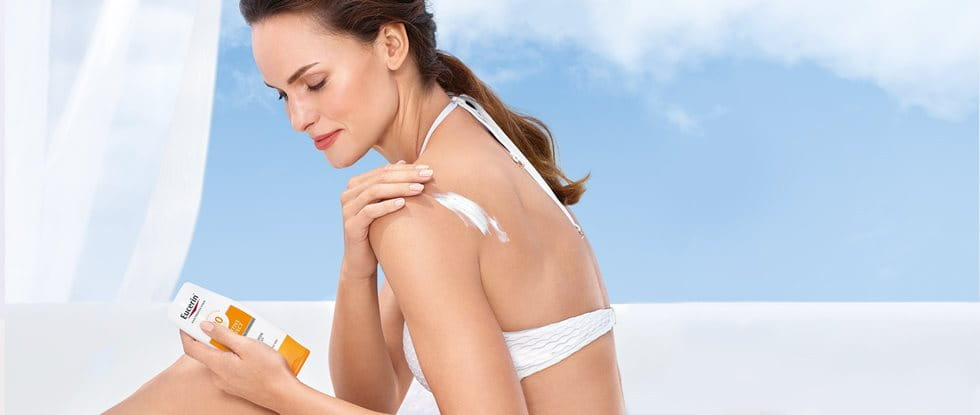 Woman applying sunscreen on her arm